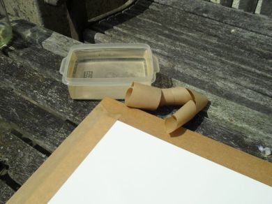 Taping down the soaked paper with brown gummed tape