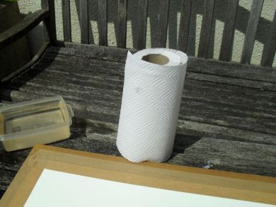 The freshly taped paper, with a roll of kitchen towel to dry it with.