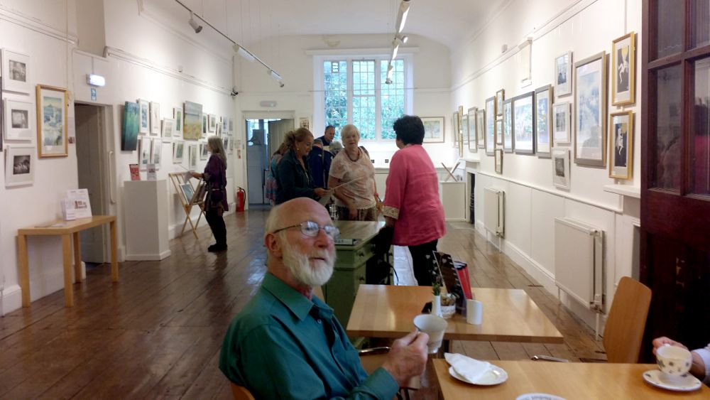 Visitors to the preview, enjoying art, tea and cake